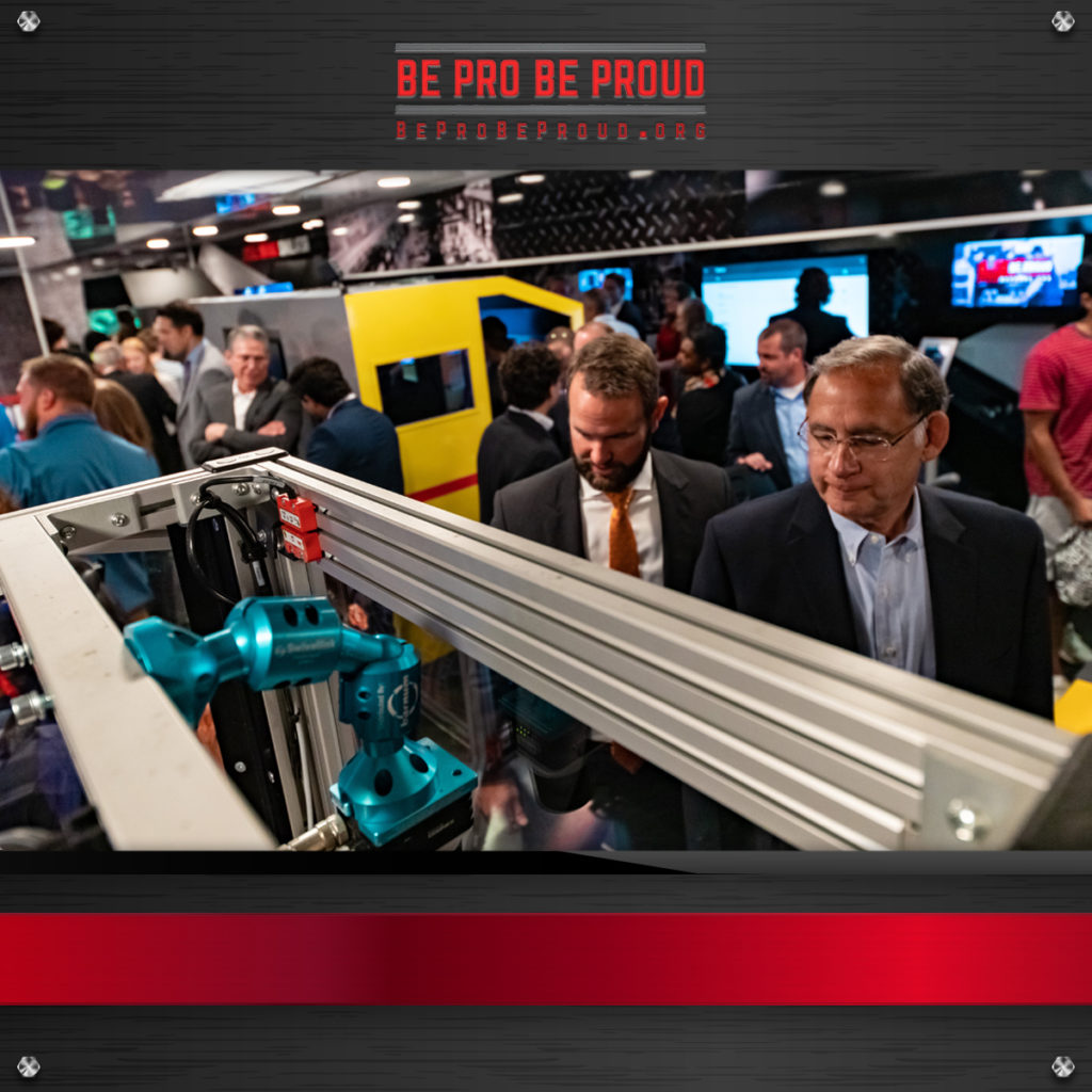 Men looking at tools and demos at the Be Pro Be Proud experiential marketing event and truck unveiling